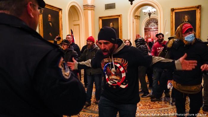 سینیٹ کے چیمبر کے باہر دالان میں مظاہرین نے امریکی کیپیٹل پولیس کا اشارہ کیا