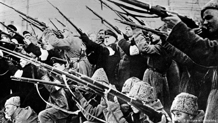 زیادہ تر موٹی اون کی ٹوپیاں پہنے ہوئے ، بندوقیں تھامنے اور اشارہ کرنے والے مرد