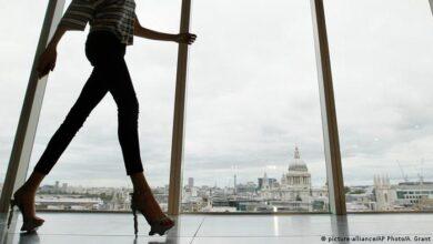 ایک پتلی جینز پہننے والی عورت ایک دالان میں چل رہی ہے