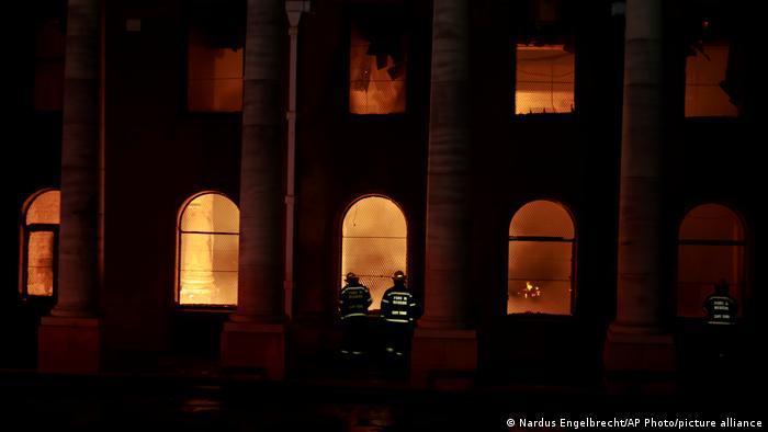 جاگر لائبریری کے ونڈوز عمارت اور دو فائر فائٹرز کو آگ لگاتے ہیں۔