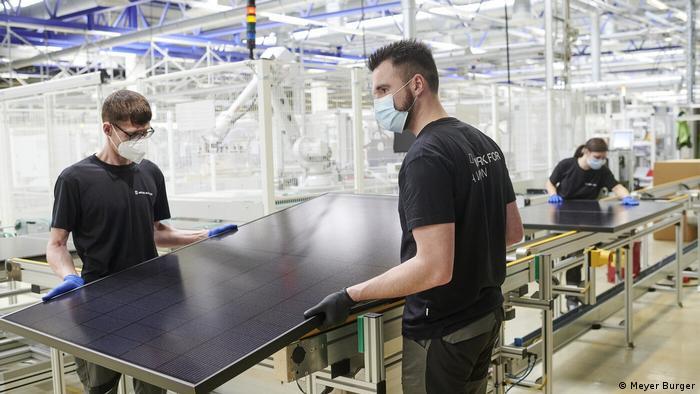 فیکٹری کے دو کارکن سولر پینل اٹھا رہے ہیں