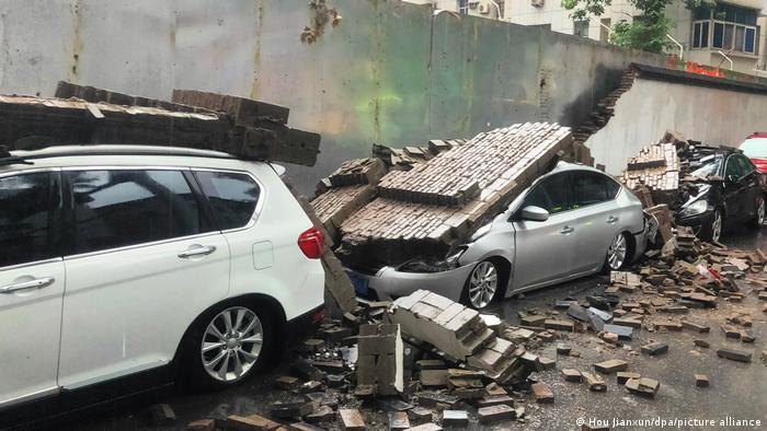 ژینگزہو ، چین: تین کاریں دیوار کے ساتھ کھڑی ہیں جو ان کے اوپر گر گئیں۔  اینٹیں پوری سڑک پر لگی ہوئی ہیں۔