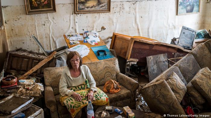 تباہ شدہ کمرے میں بیٹھی ایک عورت
