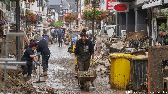 لوگ کیچڑ اور ملبے کی گلیوں کی صفائی کرتے ہیں