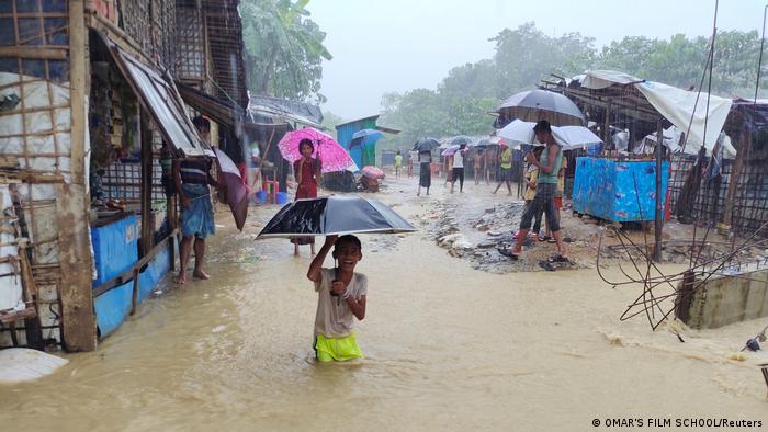 حالیہ شدید بارشوں سے متاثرہ پناہ گزین کیمپوں میں سے ایک میں ایک لڑکا سیلاب زدہ گلی میں کھیل رہا ہے۔  اس کے ارد گرد لوگ چھتریوں کے ساتھ گھوم رہے ہیں۔  مکانات عارضی عمارتیں دکھائی دیتے ہیں۔