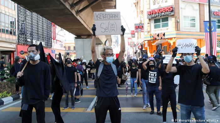 ملائیشیا کے مظاہرین نے حکومت سے استعفیٰ دینے کا مطالبہ کرتے ہوئے نشانات دکھائے۔