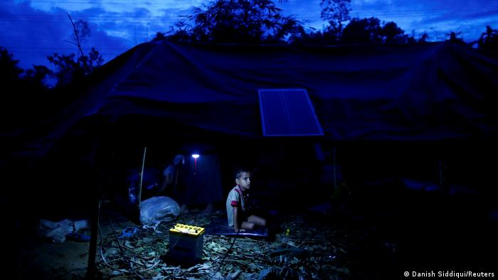 ایک لڑکا کاکس بازار کے ایک کیمپ میں عارضی خیمے کی پناہ گاہ میں بیٹھا ہے۔  رات کا وقت ہے۔  خیمے کے اوپر ایک سولر پینل ہے اور لڑکے کے ساتھ ایک چھوٹا جنریٹر ہے جو لائٹ بلب لگا رہا ہے۔